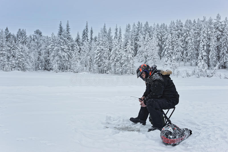 Man is ice-fishing in Ruka in Lapland stock photos