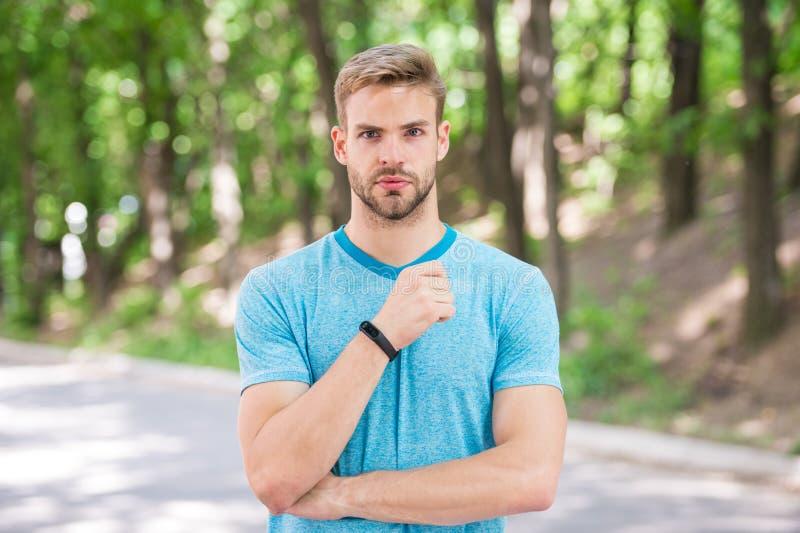 Man idrottsman nen på den strikta framsidan som poserar med sportive utrustning, naturbakgrund Idrottsman nen med borstet med kon fotografering för bildbyråer