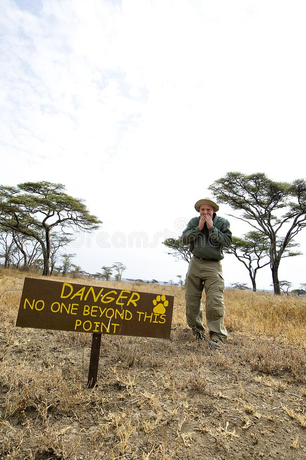 Man ignores warning sign in Africa. Man ignores danger sign in Africa royalty free stock images
