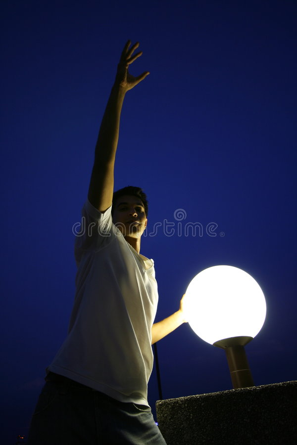 Man illuminated by night lamp. Low angle view of handsome young man stretching at night; illuminated by lamp or light globe with blue sky background royalty free stock photography