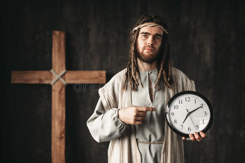 Man in the image of Jesus Christ shows on clock. Even God can not turn back time, crucifixion cross on black background royalty free stock photos