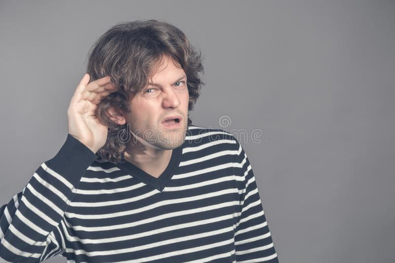 Man with impaired hearing struggling to hear frowning as he holds his hand to his ear in an attempt to improve acoustics. Gossip. Angry man holding hand to ear stock photos