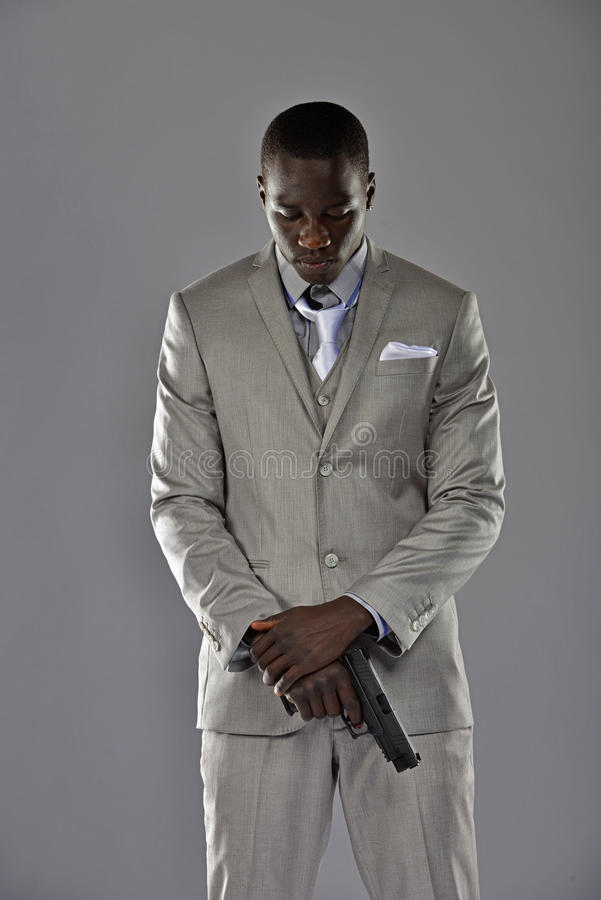Free Man In A Suit Looks Down As He Holds His Gun Royalty Free Stock Images - 30286039
