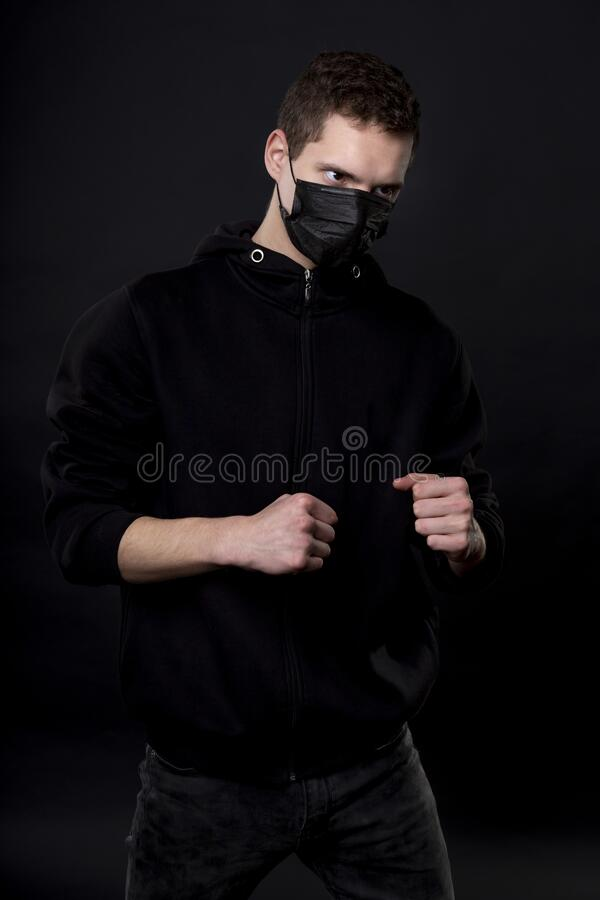Free Man In Black In A Fighting Pose With Clenched Fists. On The Young Man`s Face, A Black Medical Mask Covers His Nose And Royalty Free Stock Photos - 178718368