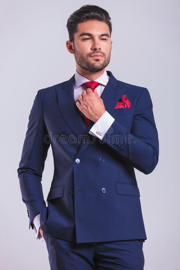 Free Man In Suit In Studio With Hand In Pocket While Fixing His Tie Royalty Free Stock Photos - 62721938