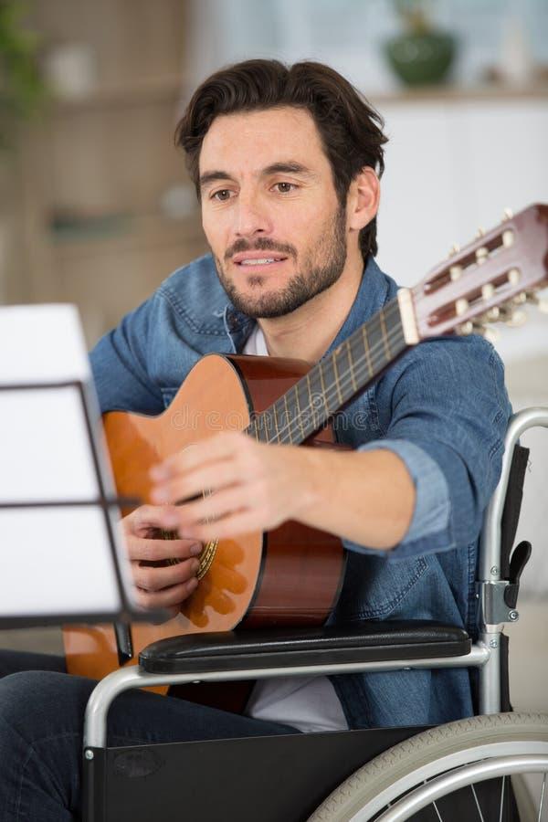 Free Man In Wheelchair Practicing Playing Guitar Stock Image - 204736281
