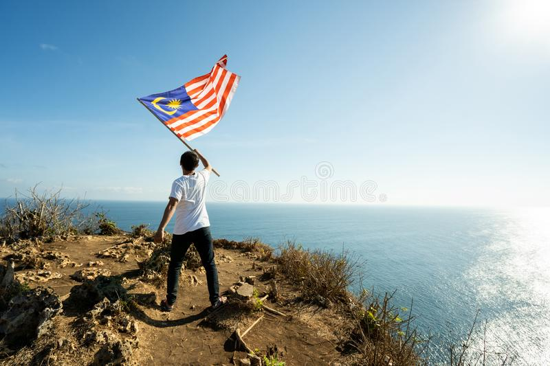 Man with indonesian flag of indonesia on top of the mountain. Asian man with indonesian flag of indonesia on top of the mountain royalty free stock photography
