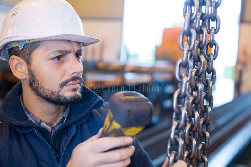 Man in industrial building holding chains stock images