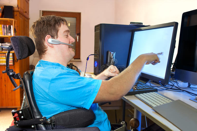 Man with infantile cerebral palsy using a computer. Spastic young man with infantile cerebral palsy caused by a complicated birth sitting in a multifunctional stock image
