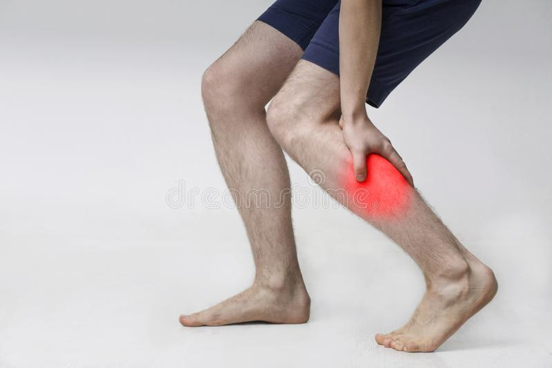 Man with injured calf, massaging painful leg muscle. With red sore spot stock photo