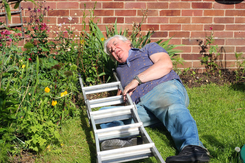 Man injured after falling from a ladder. An elderly man lying injured on the ground after having fallen from a ladder whilst doing repairs royalty free stock photography