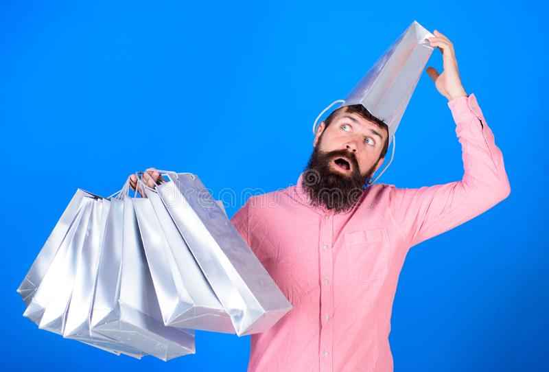 Man with insane look and open mouth wearing silver paper bag on his head. Shopaholic going crazy about seasonal sales royalty free stock images
