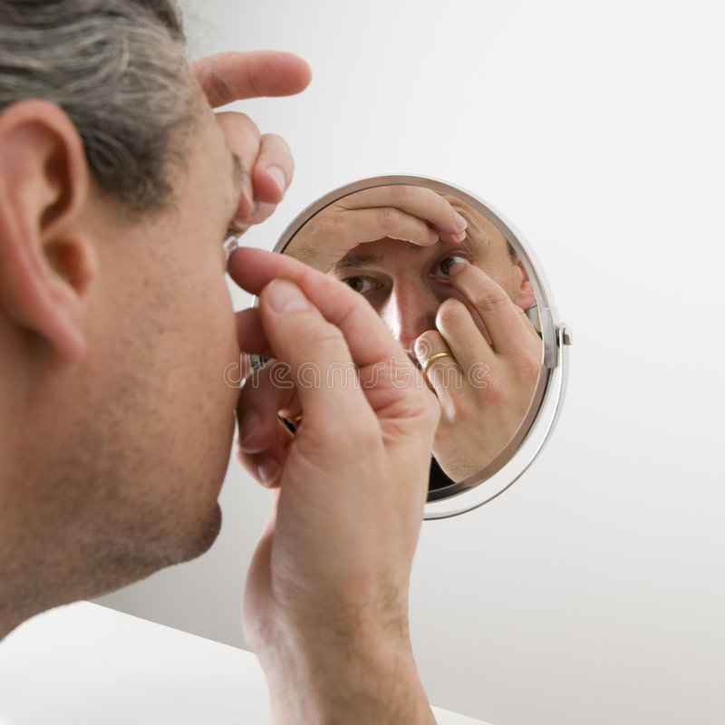Man inserting a contact lens royalty free stock photography