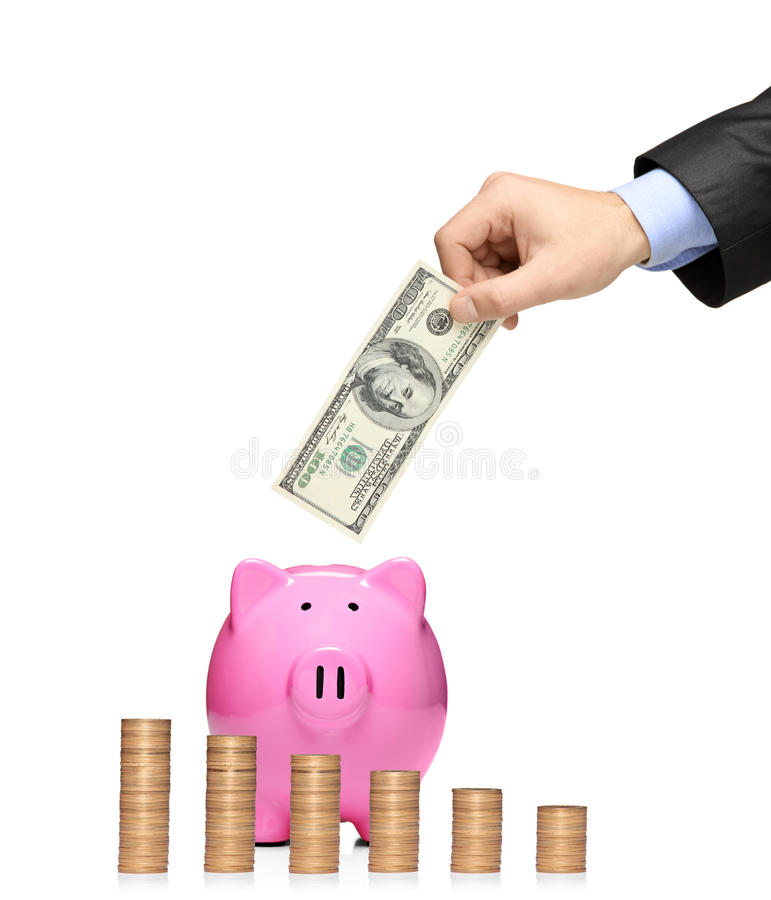 Man Inserting A Dollar Into A Piggy Bank Royalty Free Stock Photography
