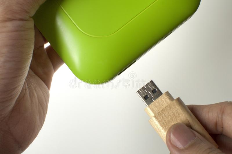 A man is inserting a flashdrive in a green powerbank stock photos