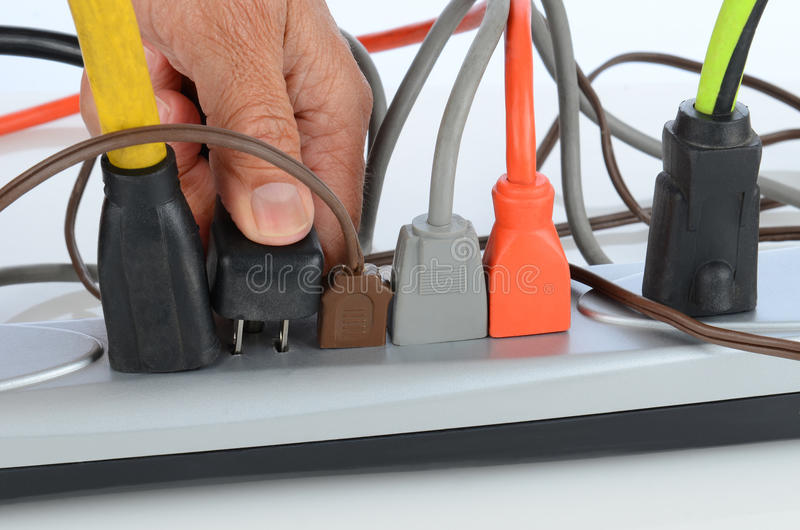Man Inserting Plug into Power Strip stock image