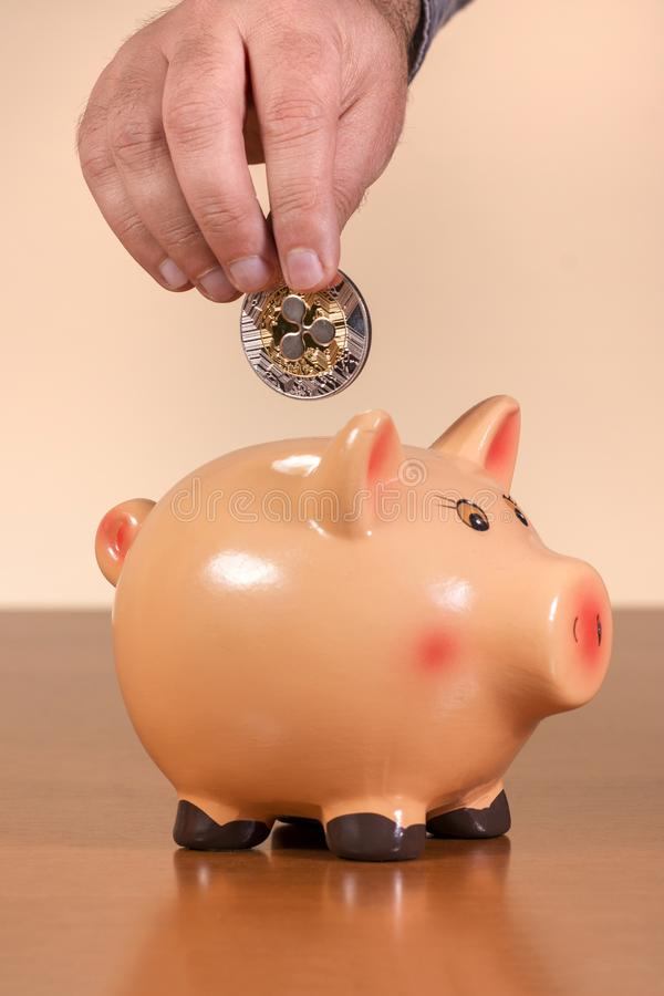man inserts ripple coin in piggy bank royalty free stock photo