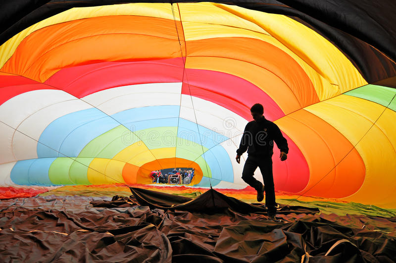 Man inside a colorful hot air balloon inflating