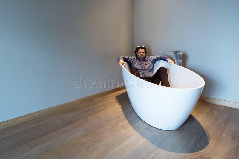 Man inside a luxury bathtub in modern apartment stock image