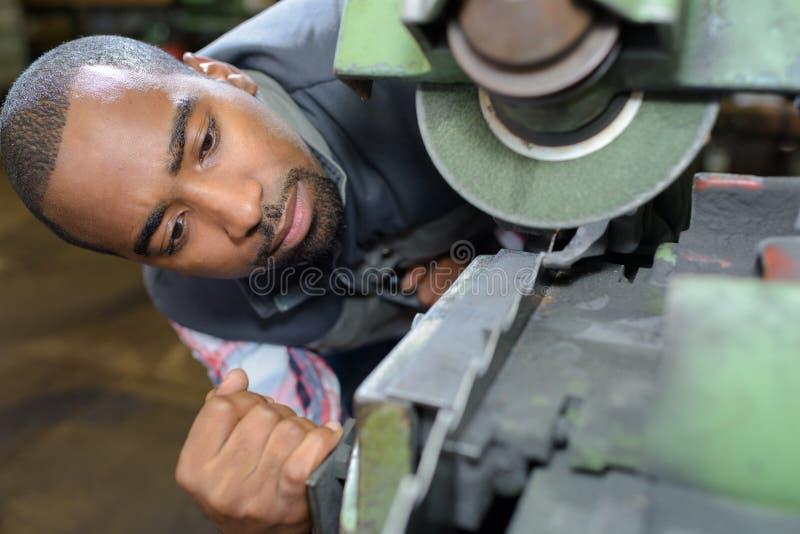 Man inspecting broken machine royalty free stock image