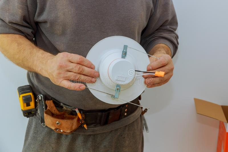Man is installing electrical light in the ceiling replacing repair works in the flat royalty free stock image