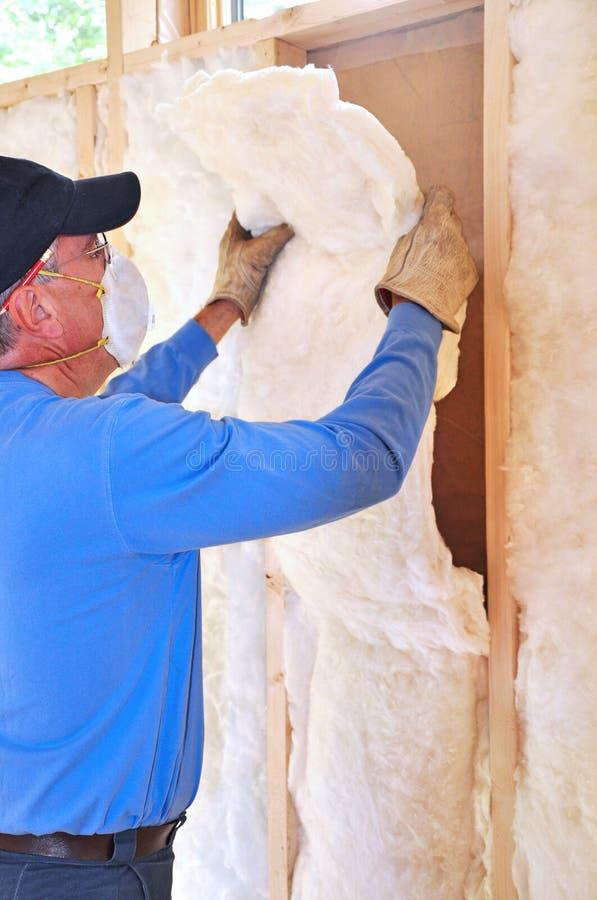 Man installing fiberglass insulation royalty free stock photography