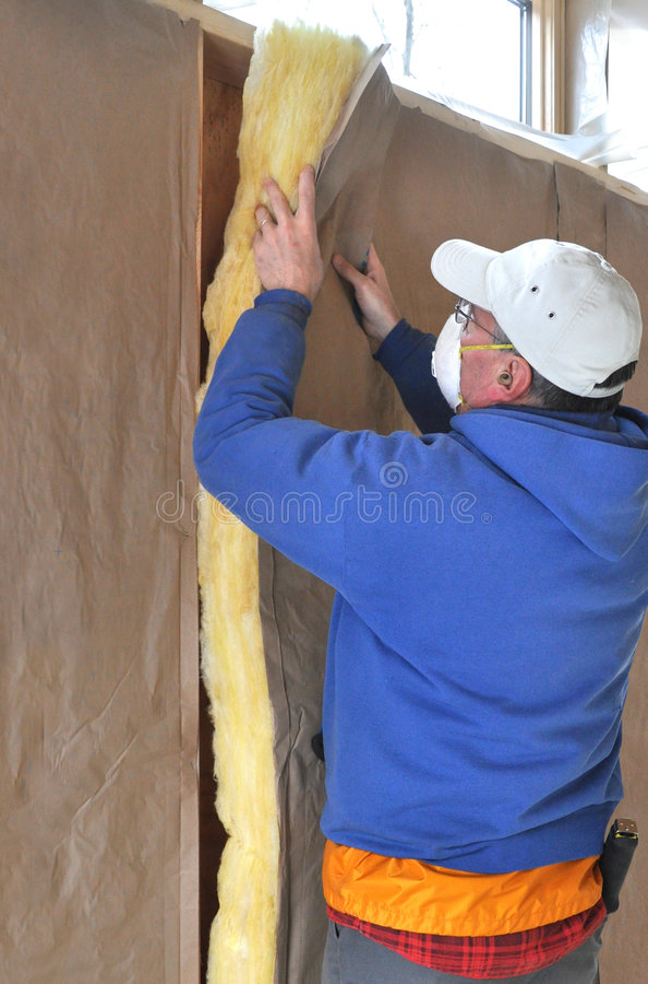 Man installing fiberglass insulation. In wall cavity royalty free stock photo