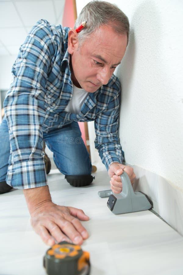 Man installing light laminate flooring in room stock photo