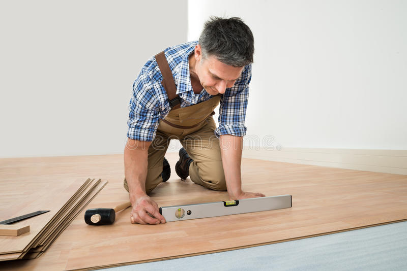 Man installing new laminated wooden floor royalty free stock image