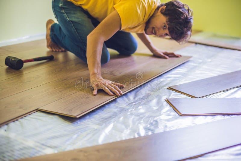 Man installing new wooden laminate flooring. infrared floor heat royalty free stock photography