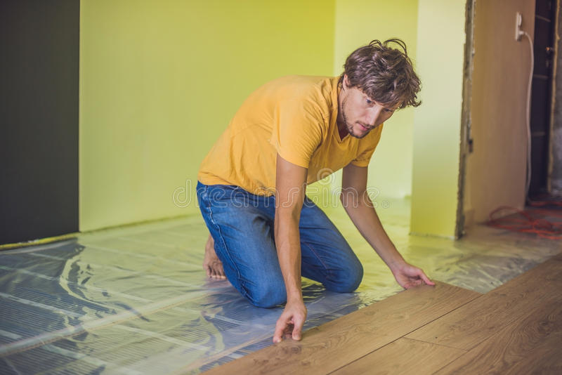 Man installing new wooden laminate flooring. infrared floor heat royalty free stock image