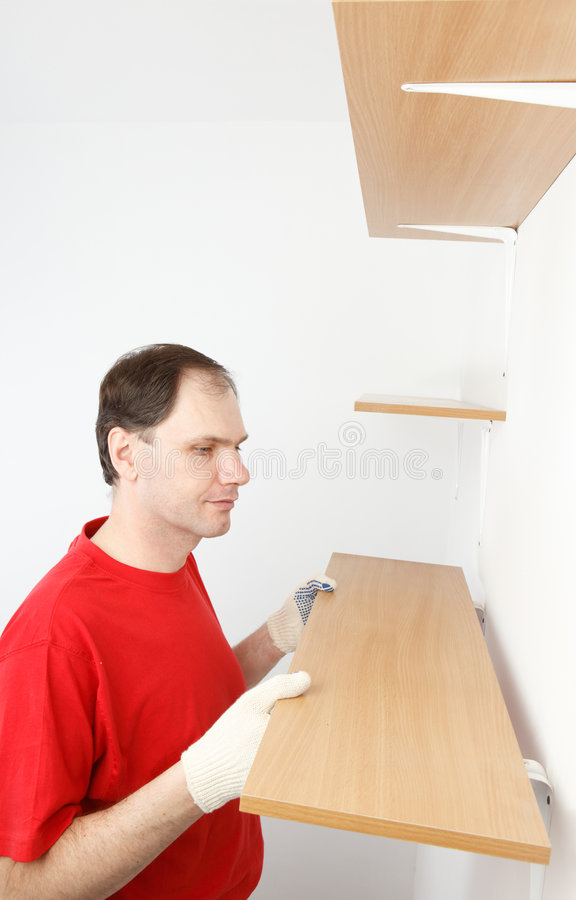 Man installing the shelf royalty free stock image