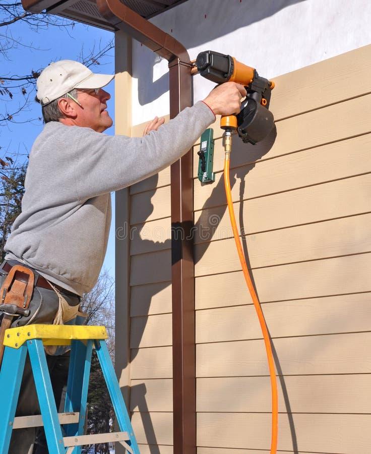 Man installing siding with nail gun royalty free stock images