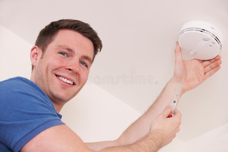 Man Installing Smoke Or Carbon Monoxide Detector stock images