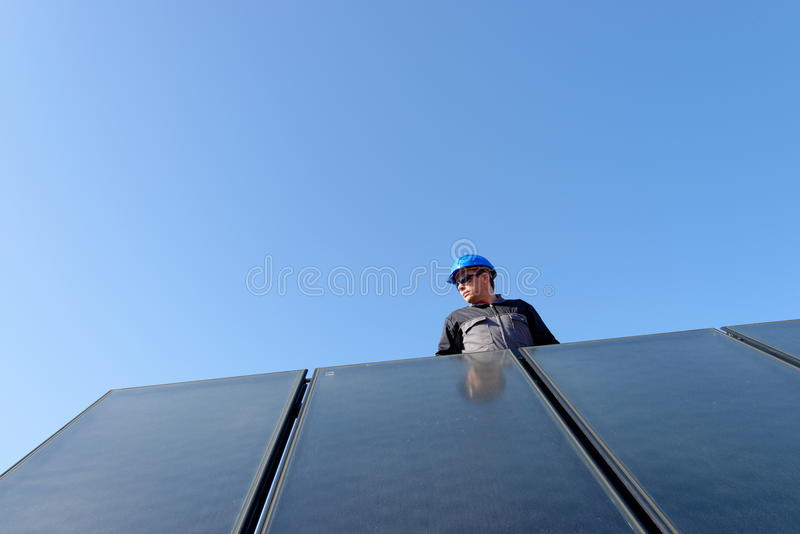 Man installing solar energy photovoltaic panels stock image