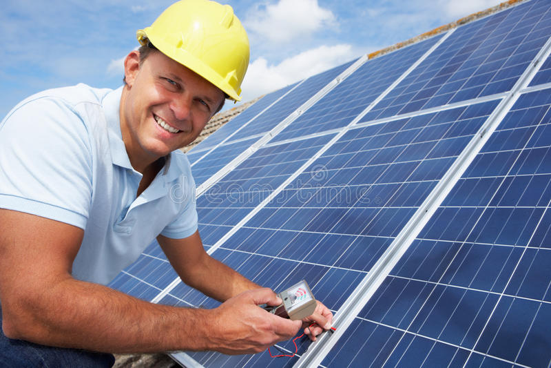 Man installing solar panels royalty free stock image