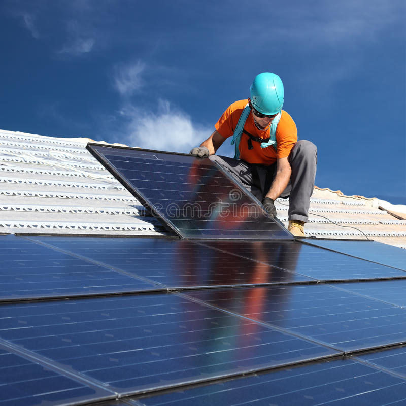 Man installing solar panels royalty free stock photo