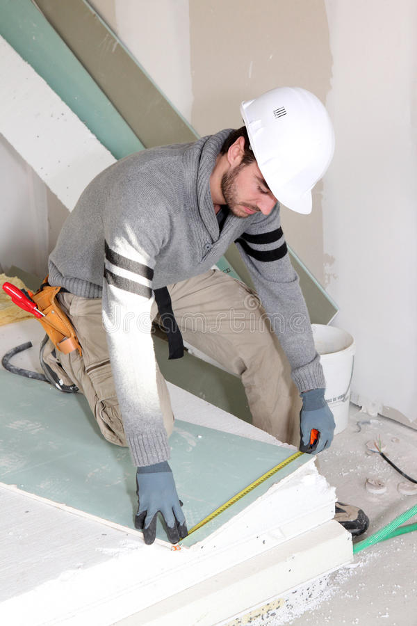 Man installing wall panels. Man installing dry wall panels royalty free stock photography