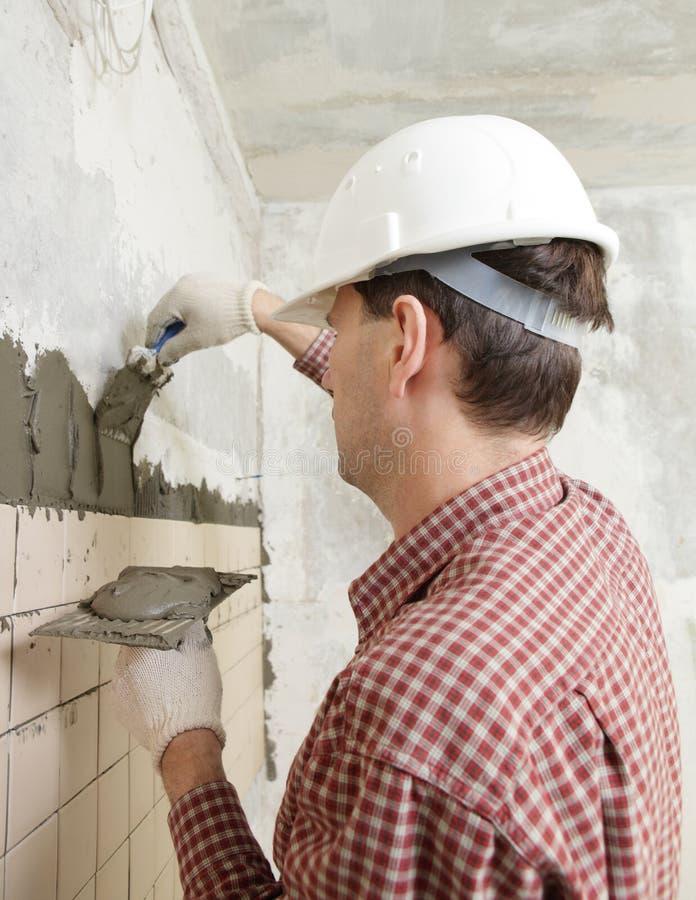 Man installs ceramic tile stock photos