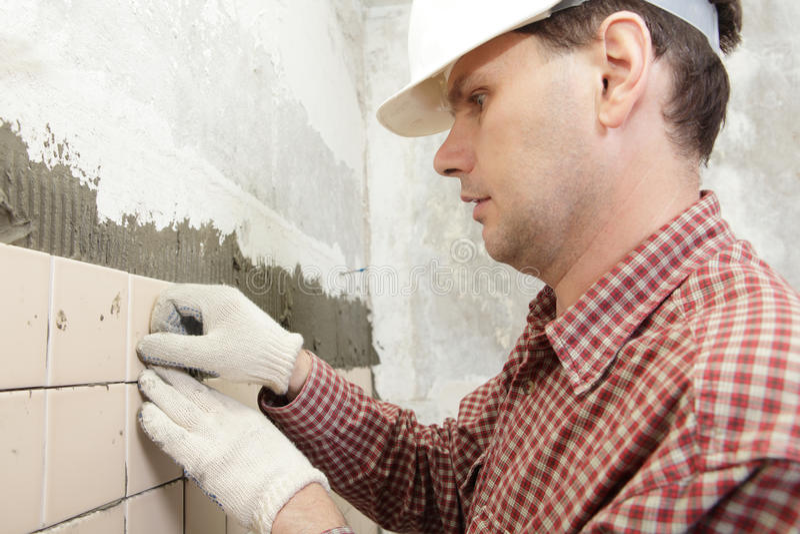 Man installs ceramic tile stock photo