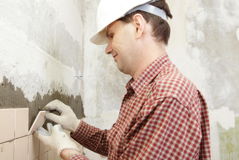 Man installs ceramic tile royalty free stock images