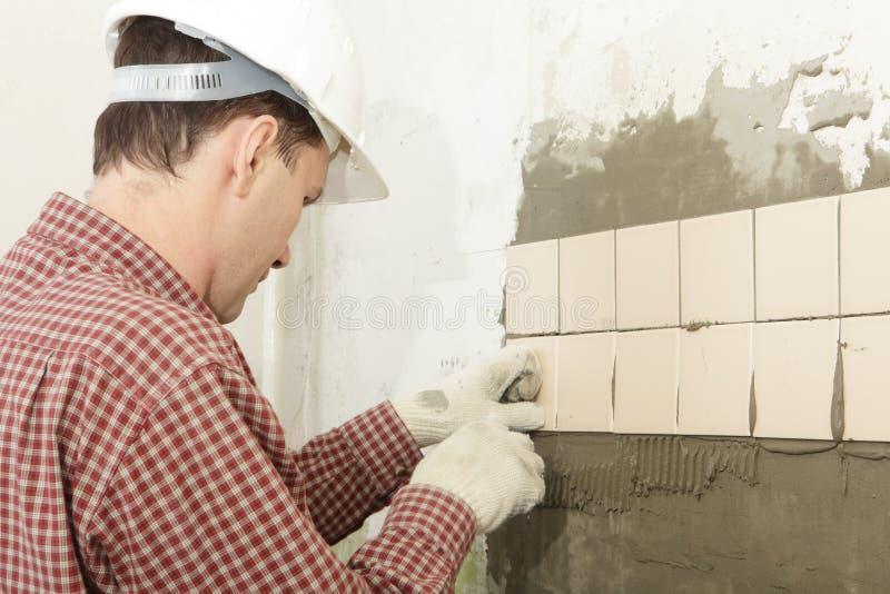 Man installs ceramic tile royalty free stock photos