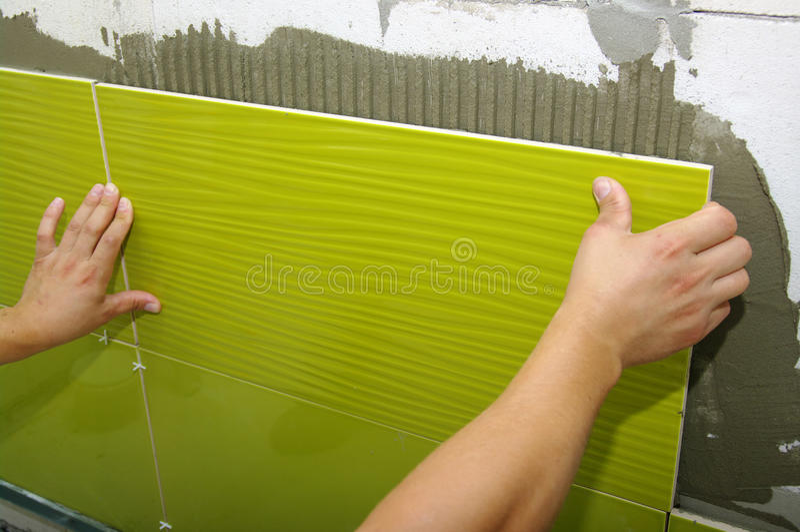 Ceramic tile. A man installs ceramic tile royalty free stock photos