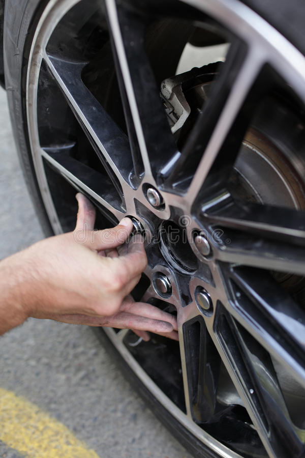 Download Man installs spare wheel stock image. Image of replace - 21697927