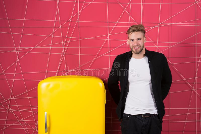 Man interior designer near fridge. Bright fridge household appliances interior object. Designer adding accent to. Interior. Man lean retro vintage yellow royalty free stock photography