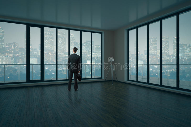 Man in interior. Thoughtful businessman in modern unfurnished interior with wooden floor, concrete walls and panoramic windows with city view and daylight. 3D royalty free stock image