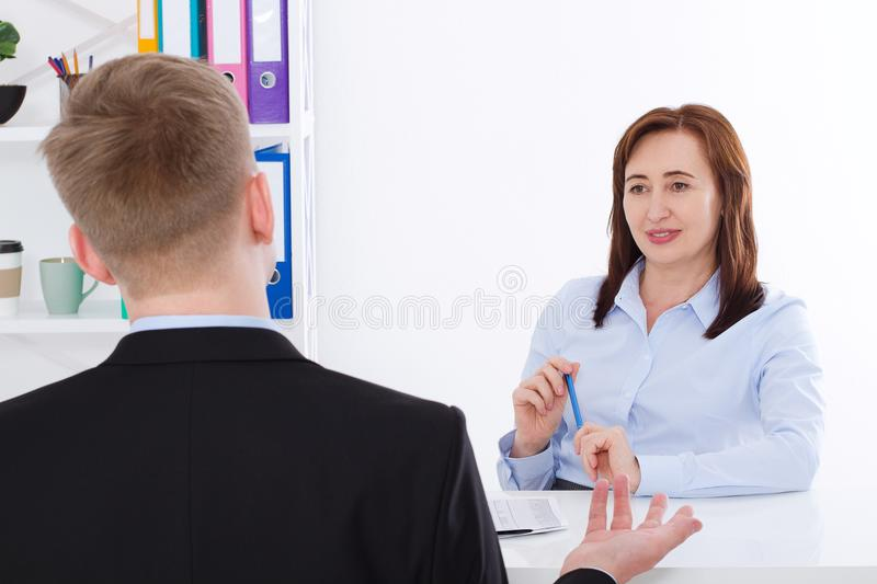 Man is interviewed at office background. Businesswoman and businessman have meeting and conversation. Copy space and mock up. stock photos