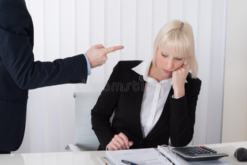 Man Intimiderende Vrouw in Bureau stock fotografie