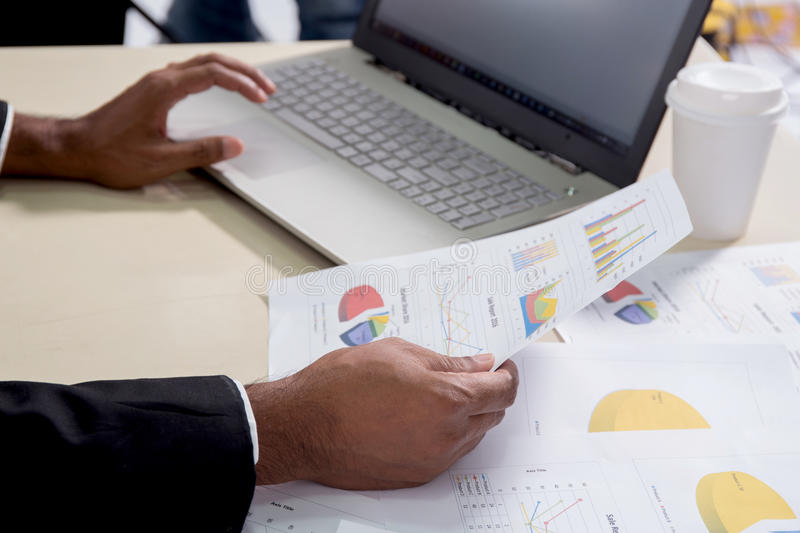 Man investment consultant analysis company annual financial report. Balance sheet statement working with documents graphs. Stock market, office, tax, education stock photo