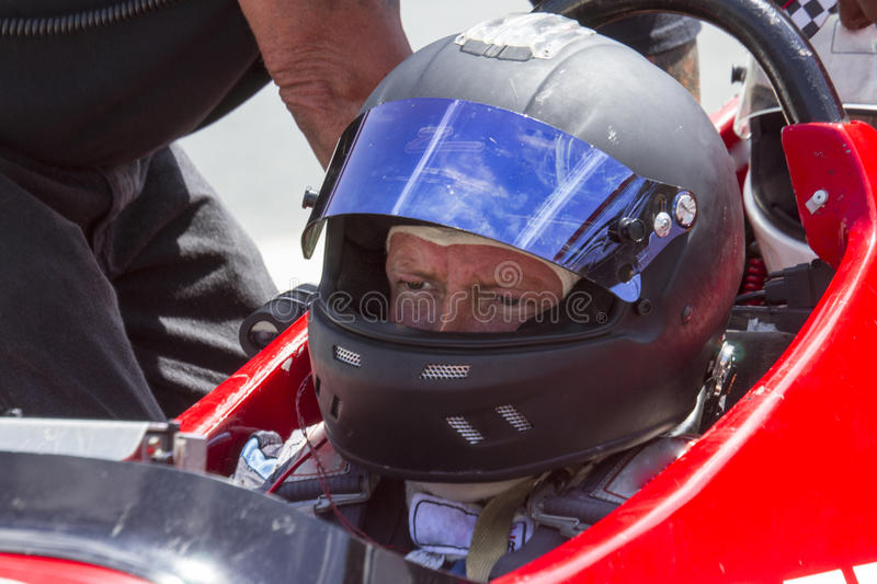 Man in IRL race car with helmet stock photography